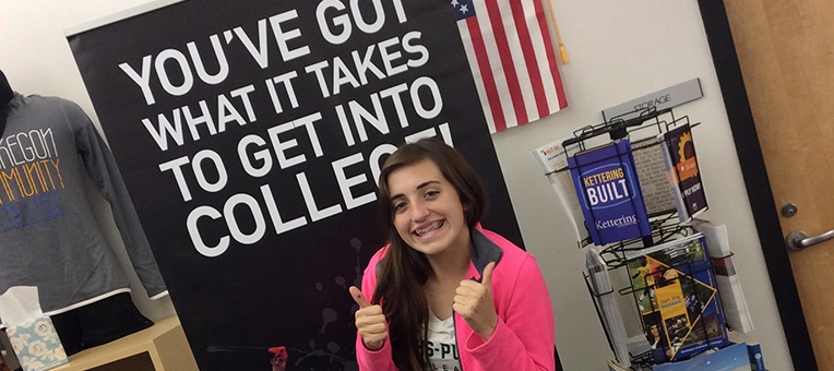 "A young lady gives two ""thumbs-up"" after completing her college application."