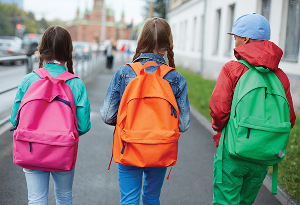 Three kids with colorful backpacks walking to school