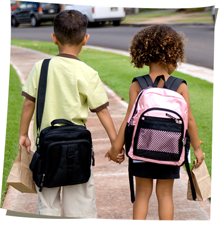 Boy and girl with backpacks holding hands and walking down the sidewalk to school