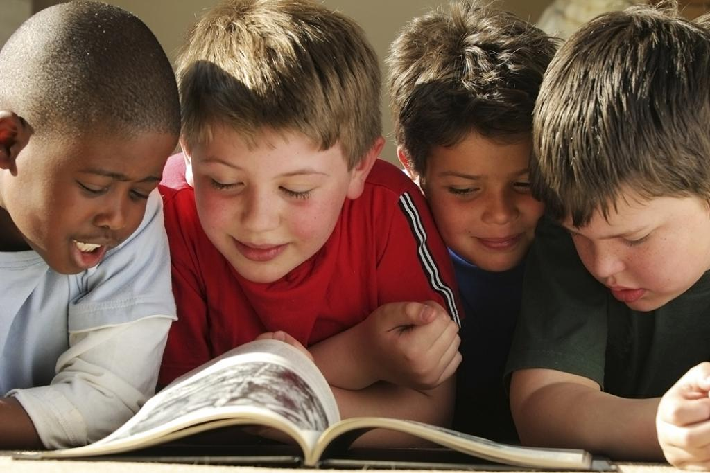 Group of four boys reading a book