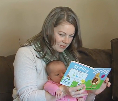 Mom reading book to infant